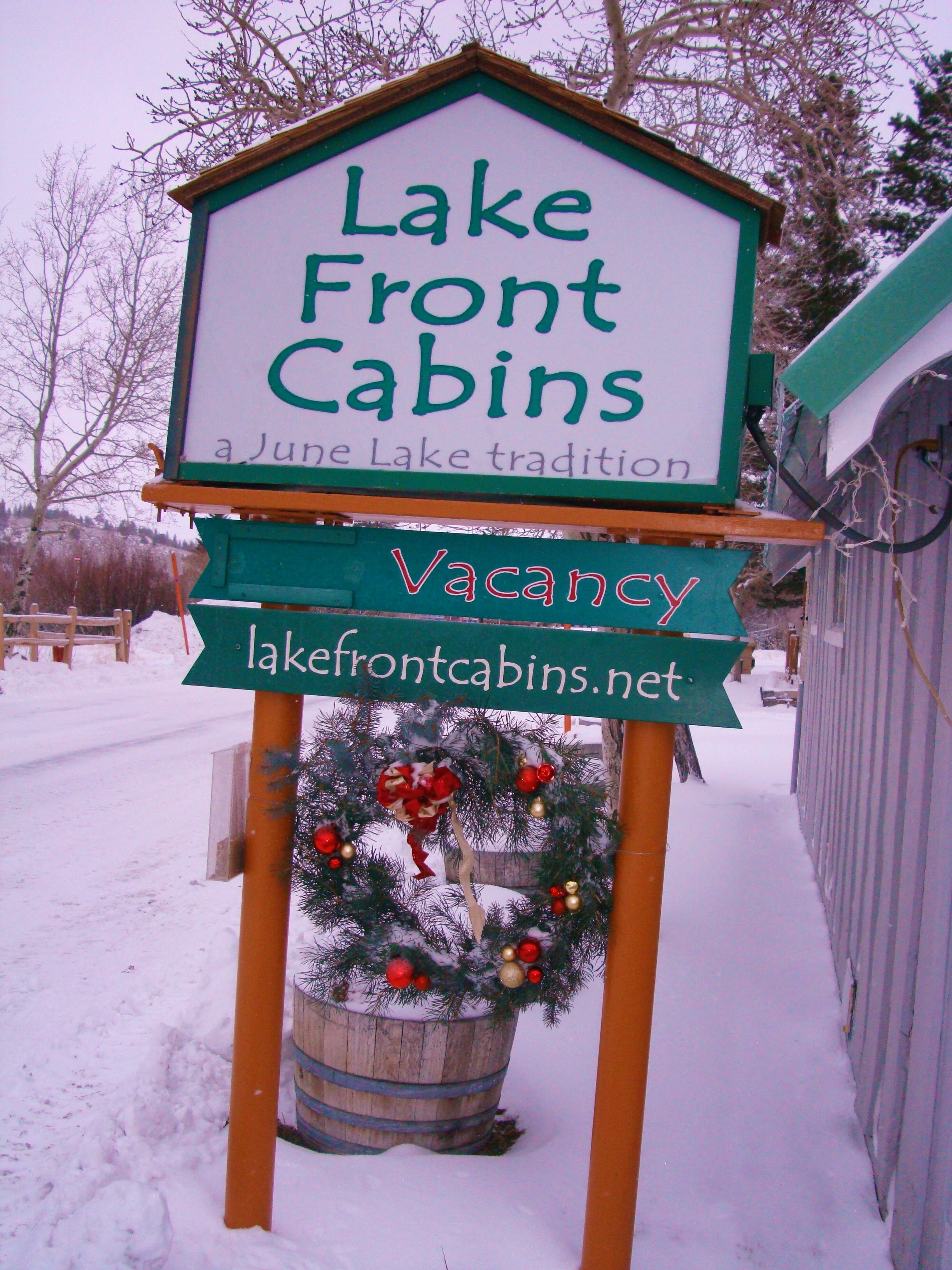 Entrance sign to Lake Front Cabins in the winter.
