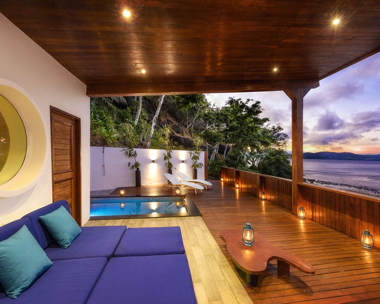 The deck of an Oceanfront Retreat at The Remote Resort Fiji Islands with large daybed, pool and ocean views