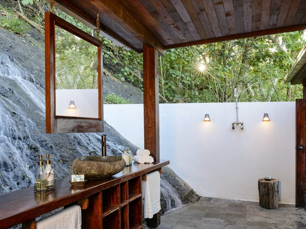 Outdoor bathroom in an Oceanfront Villa at Remote Resort Fiji Islands featuring open-air shower and vanity (toilet inside)
