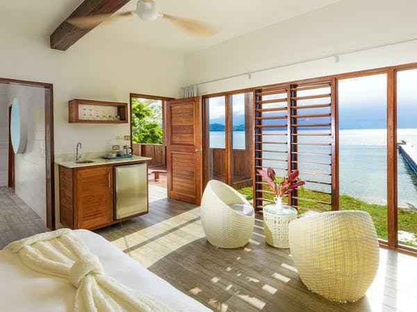 The bedroom and lounge area of an Oceanfront Retreat at The Remote Resort Fiji Islands with minibar and ocean views