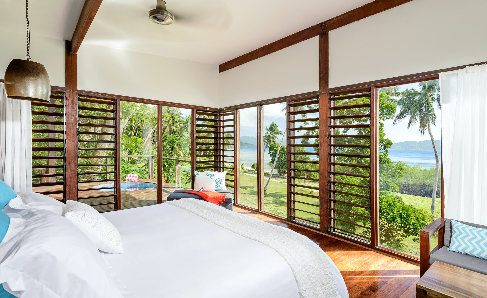 Bedroom of an Oceanfront at The Remote Resort Fiji Islands featuring floor to ceiling screened louvers and glass