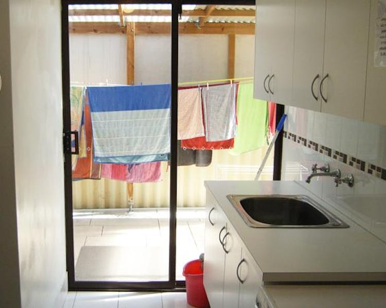 Shared Laundry with washing machine, dryer, iron and enclosed clothes line to protect your clothes from the harsh sun