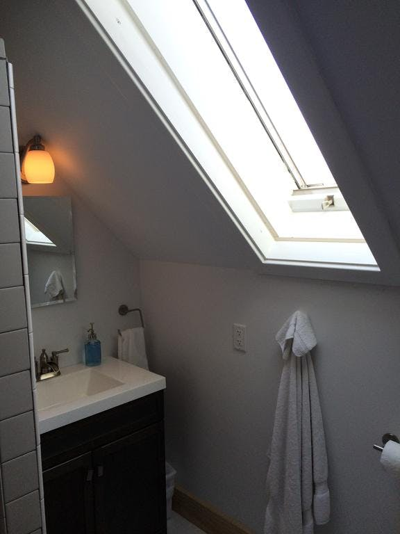 Private second floor bathroom with tiled shower and large skylight