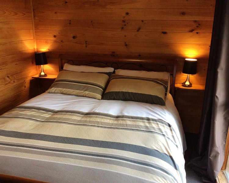 Queen bed in Trappers Lodge self-contained house