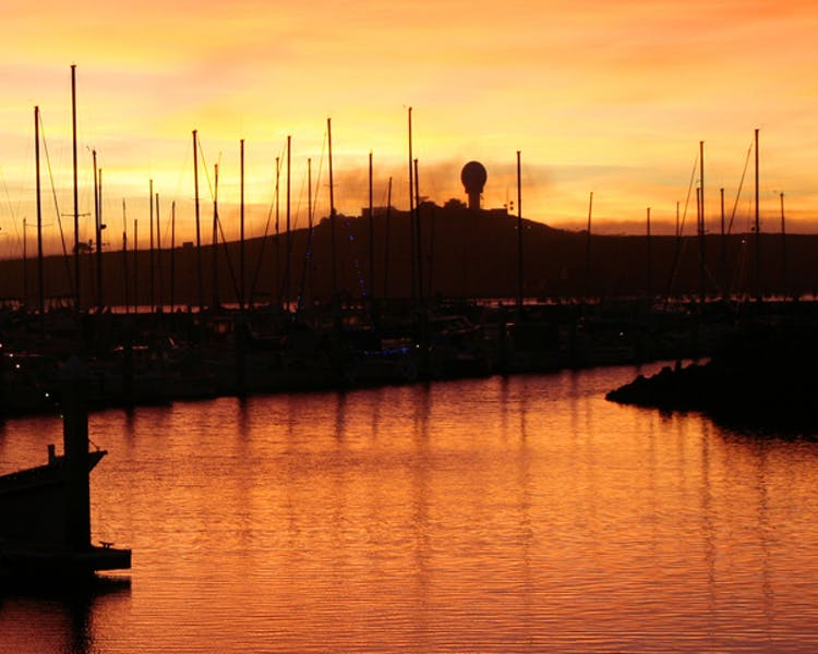 Sunset behind ship masts in Pillar Point Harbor