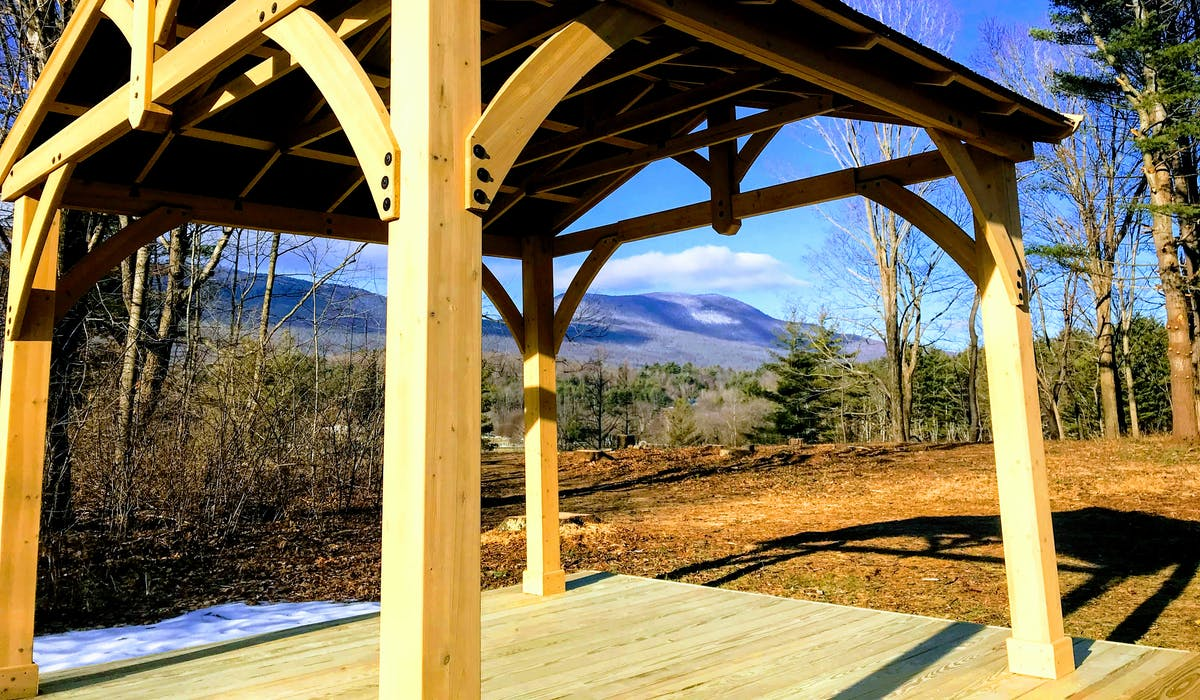 Image shows a wooden pavilion overlooking the mountains.