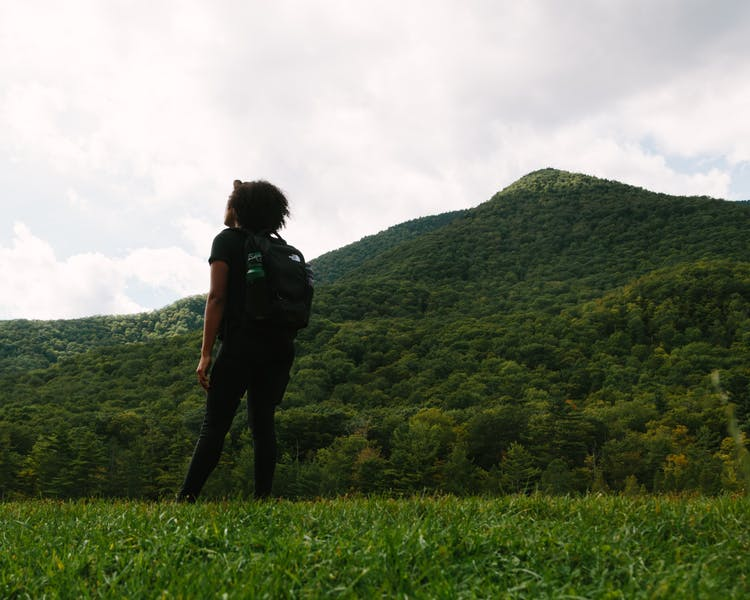 Image of the back of a woman with a backpack on, staring at the green mountains.