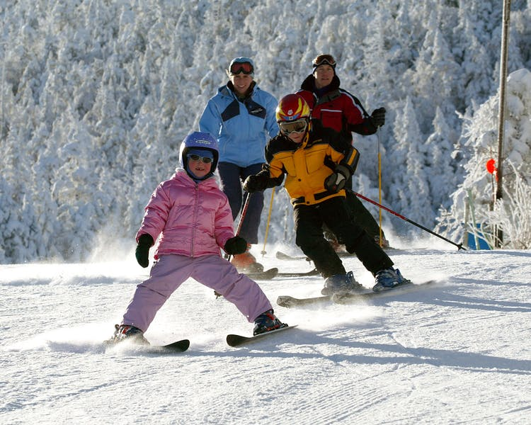 Image of a family of four skiing down snowy mountain slope.