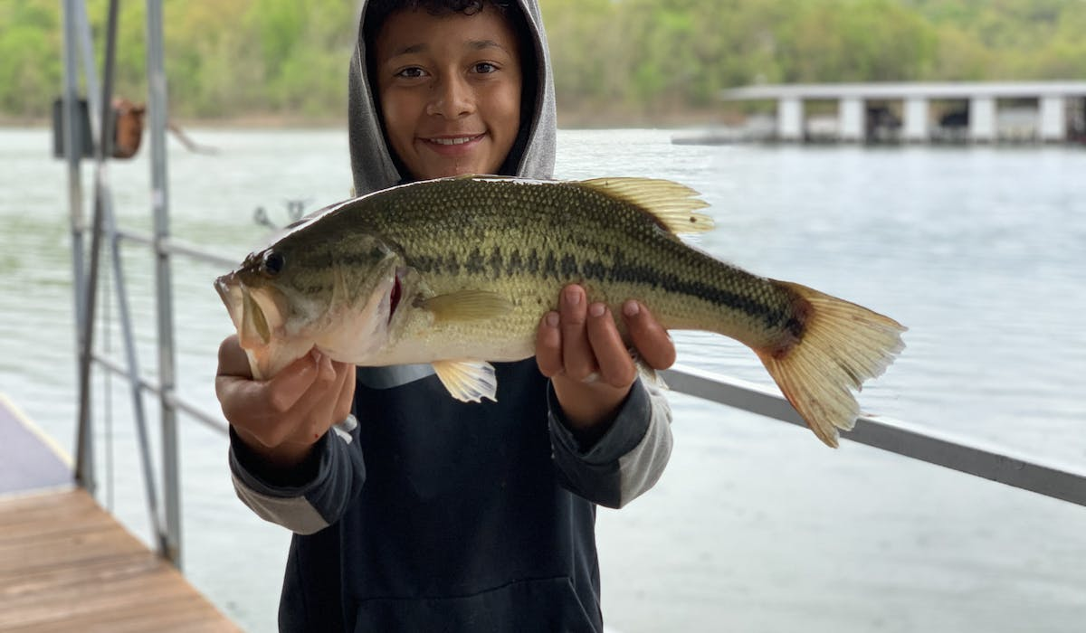 boy fishing holding large mouth bass table rock lake fishing