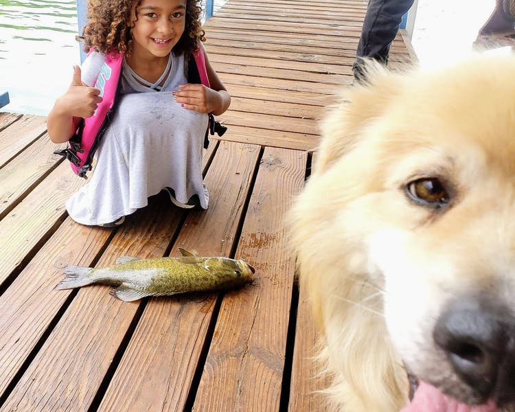 A girl, her dog, and a fish.