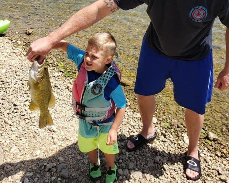 boy fishing with dad holding small mouth bass table rock lake fishing