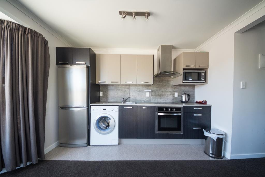 View of the galley style kitchen in unit 2, full size fridge, oven, cook top, washing machine