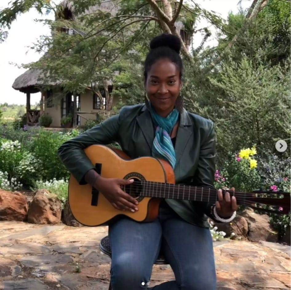 Artist Zizzy playing her guitar at Olepangi Farm