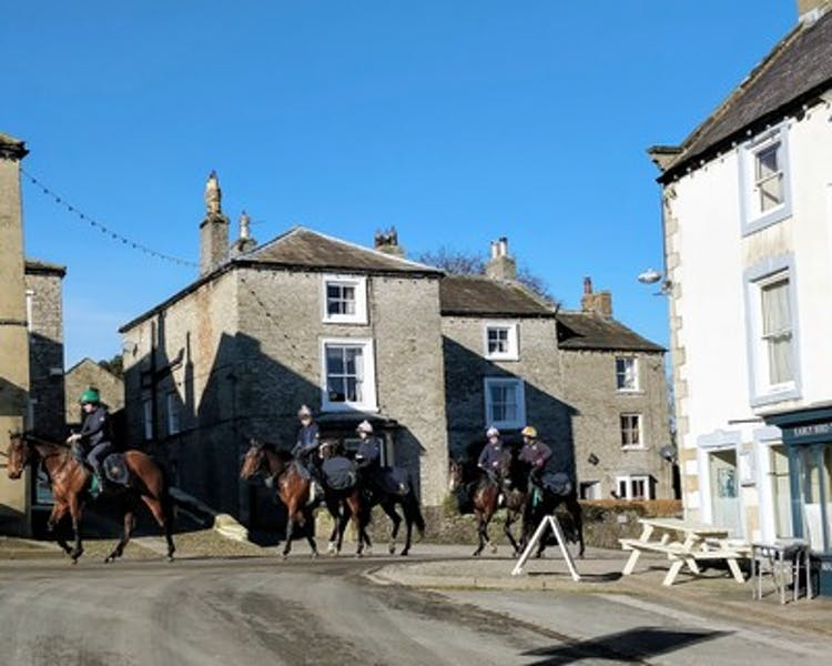 Middleton Racehorses walking past The Wensleydale Hotel and Tack Room Restaurant & Bar, Middleham, Yorkdhire Dales