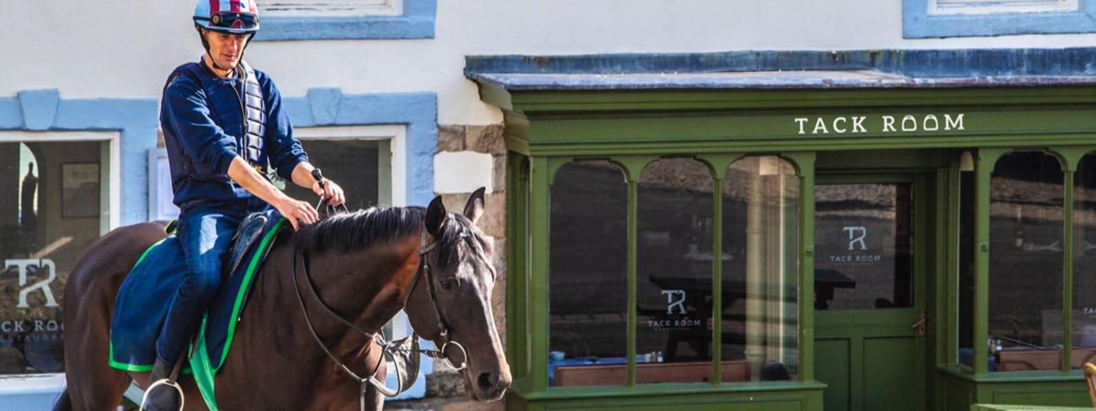 Middleham Racehorse walking past The Wensleydale Hotel, The Tack Room Restaurant & Bar, Wensleydale, Yorkshire Dales