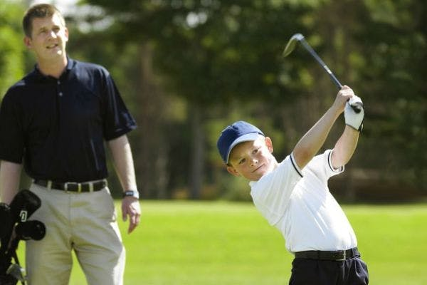 Kid playing golf at Carrick golf course with coach