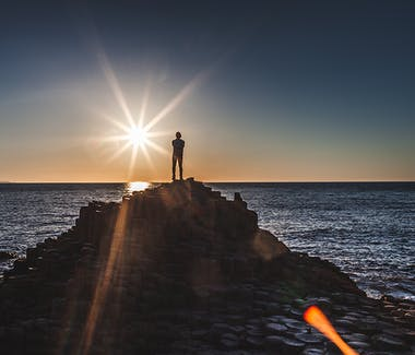 A man standing alone on top of the giants causeway during the sunset