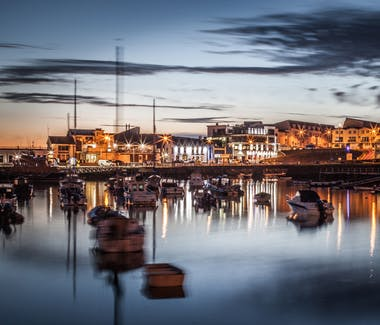 The harbour of Portrush in a atmospheric light of the setting sun and public lights