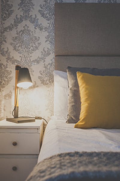 Pillows are on the bed of a beautifully decorated double room with ensuite, a table lamp creates a cozy atmosphere
