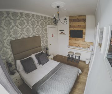 A beautifully decorated double room with ensuite in a cozy atmosphere. Two stools standing underneath the TV