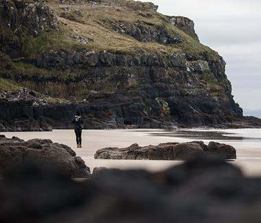 A person walking on a beach surrounded by rocks and cliffs