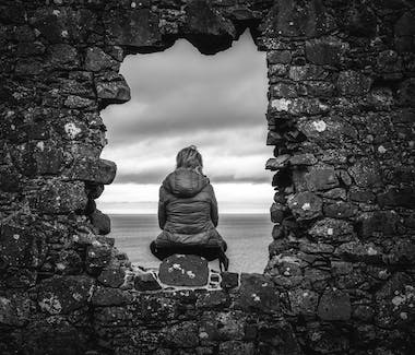 A woman sitting in an old window of the Dunluce Castle looking at the Atlantic