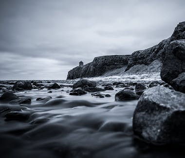 Stones lie in a river on the beach. In the background on the cliff stands the Mussenden Temple