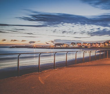 The promenade of Portrush in a wonderful light setting by public lights and the sunset.