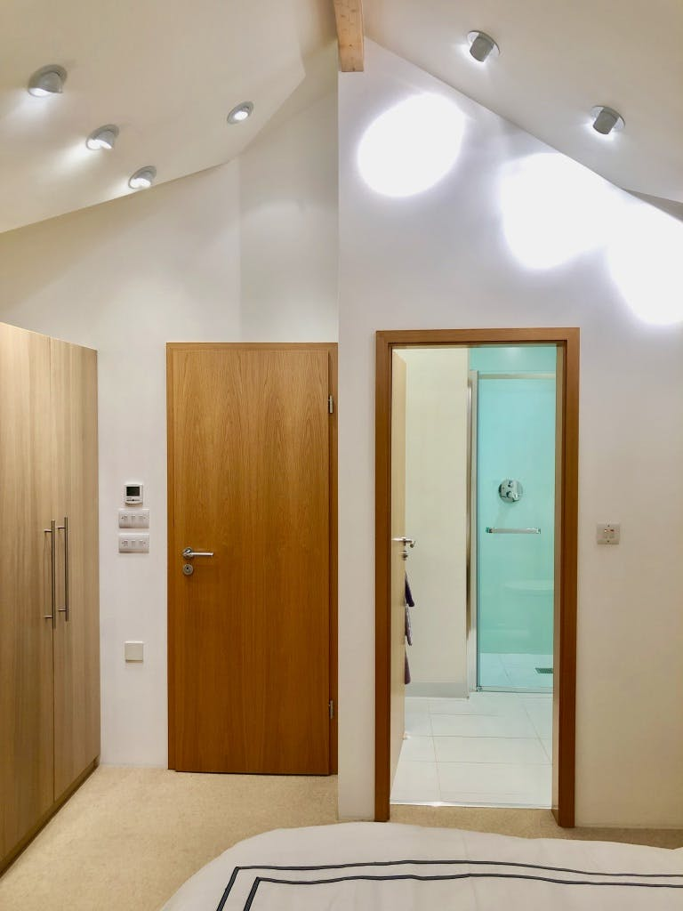 Bedroom 2 - picture of open en-suite door with vaulted ceiling and downlights