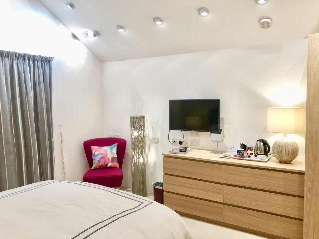 Bedroom 2 showing showing TV area with vaulted ceiling, down lights and designer standard lamp