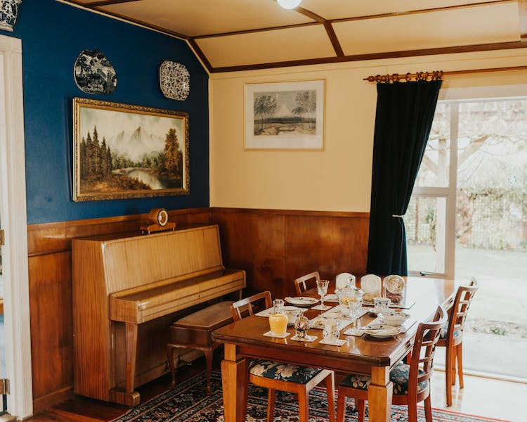 Finely decorated guest lounge with old paintings, piano and breakfast table at Tongariro Crossing Lodge