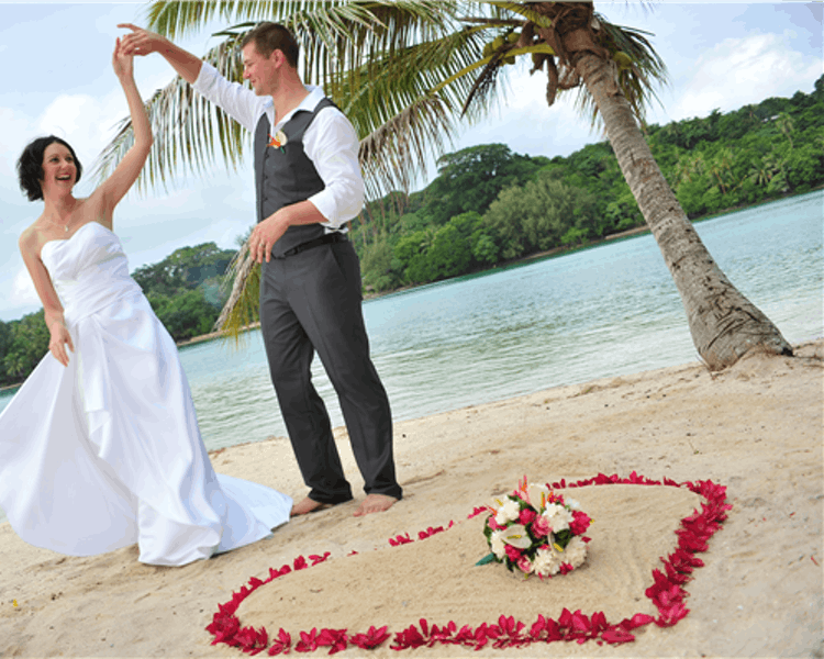 Ceremony on Coconut Beach with floral heart in the sand #erakorbeachweddings #weddingceremonyonthebeachsouthpacific #Vanuatu