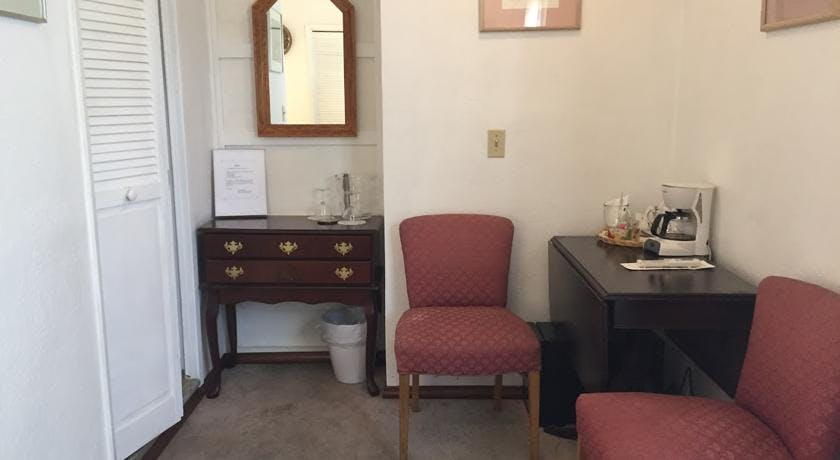 Table, chairs, dresser, and mini-fridge in Prospector Room