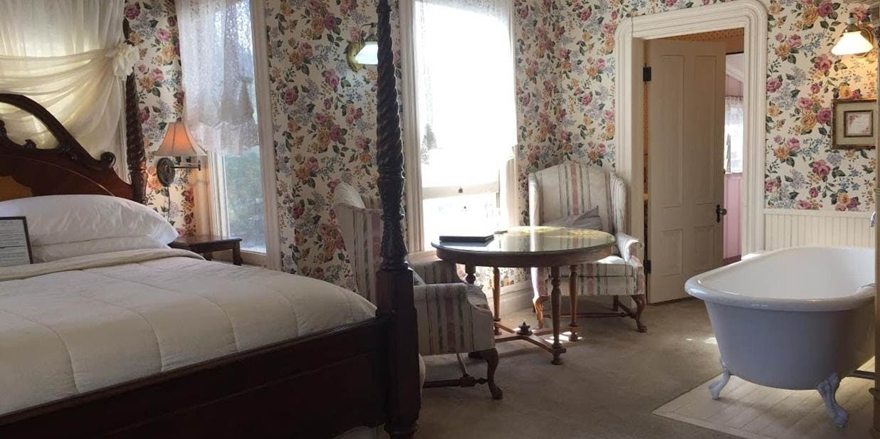 Four post king bed and table in Bradford Suite