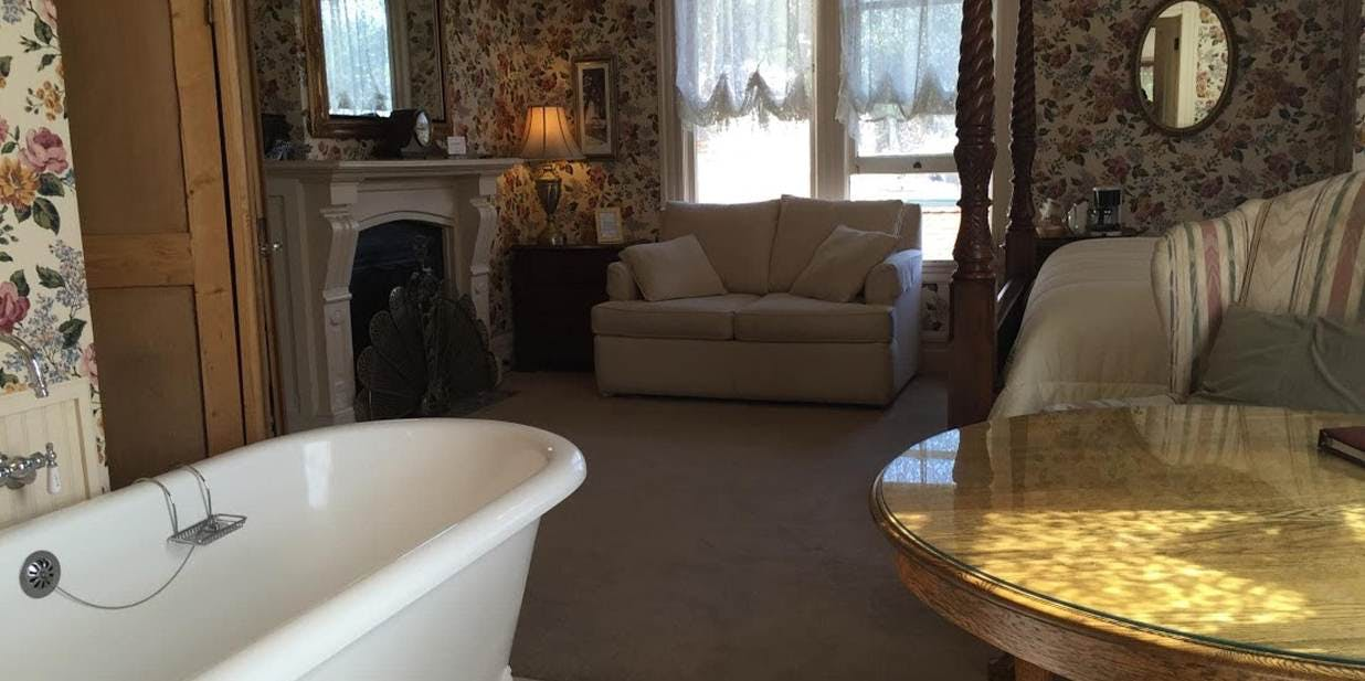 Claw foot tub, fireplace, and sofa sleeper in the Bradford Suite