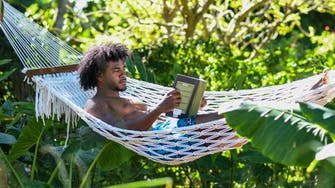 Lying on a hammock reading a book