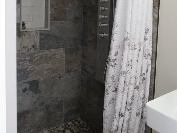 St Jacobs warm tones carry into the walk in shower with body shower panel.