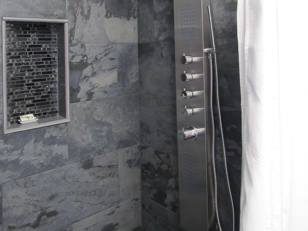 Dark slate stone for the walk in showers. A large body shower panel with rainfall or waterfall abilities.