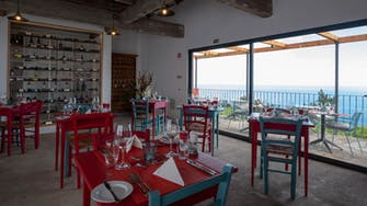 View of inside the restaurant with view of the sea beyond, rustic decoration