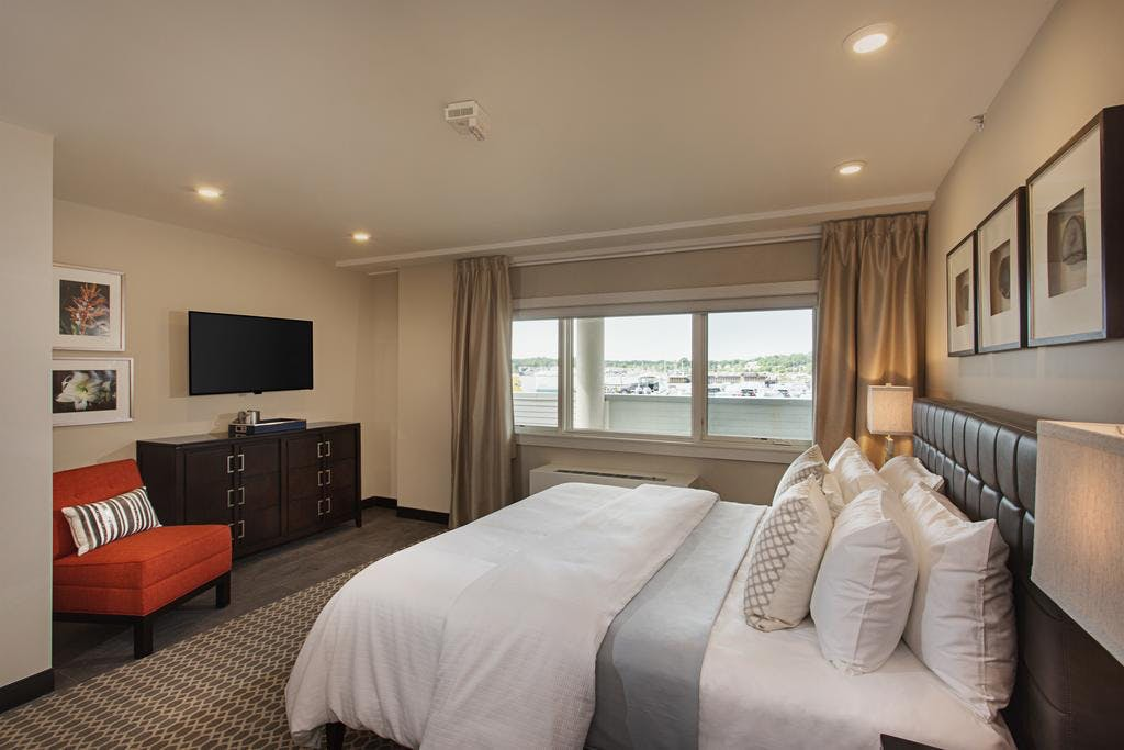 The Avalon, a king bedded spacious room with bistro table and picture window with a partial water view