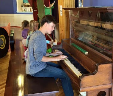 Sandcastles Children's Museum - boy plying the piano