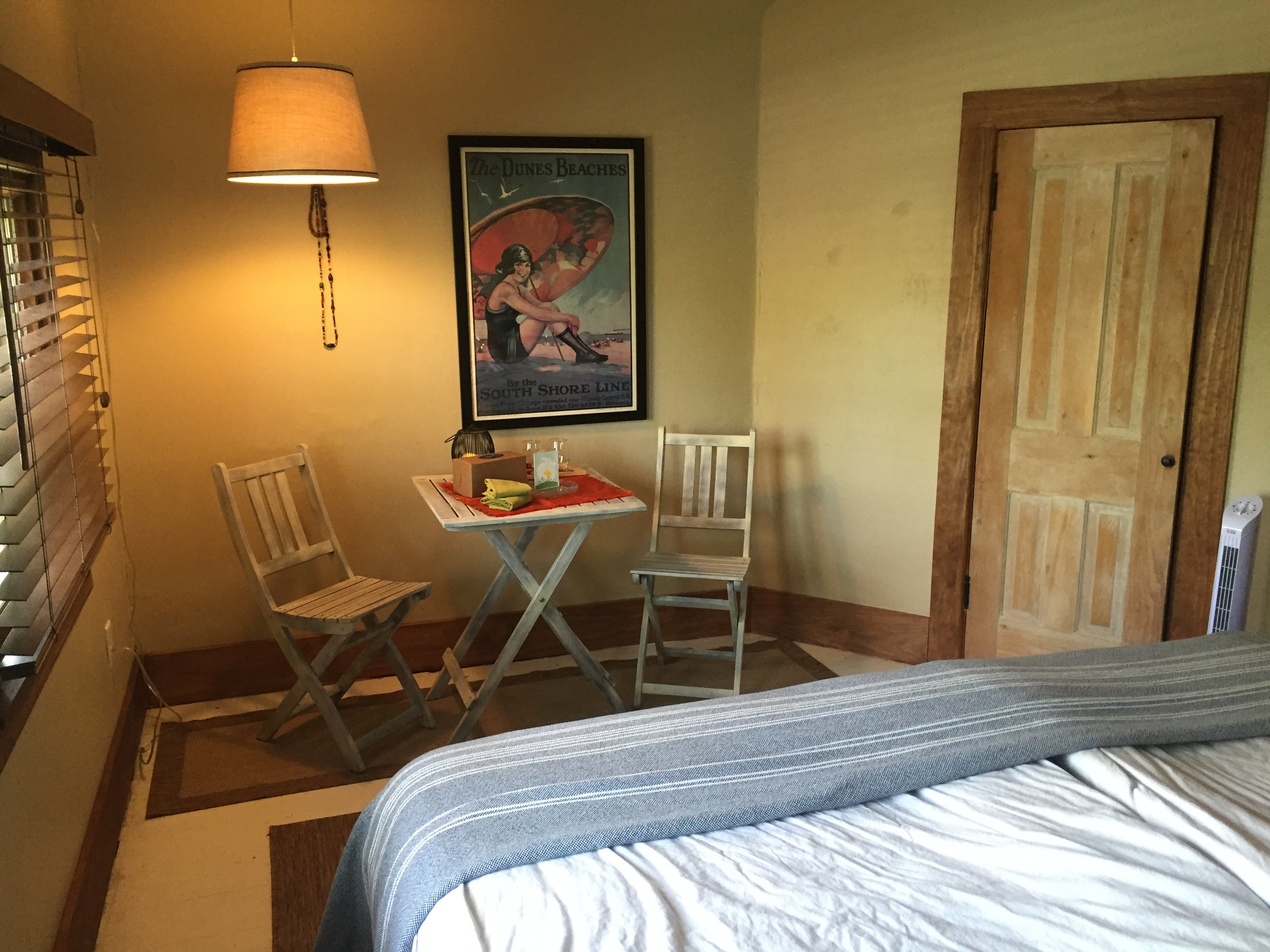 Second floor guest room with king bed, bistro set, and guest snacks