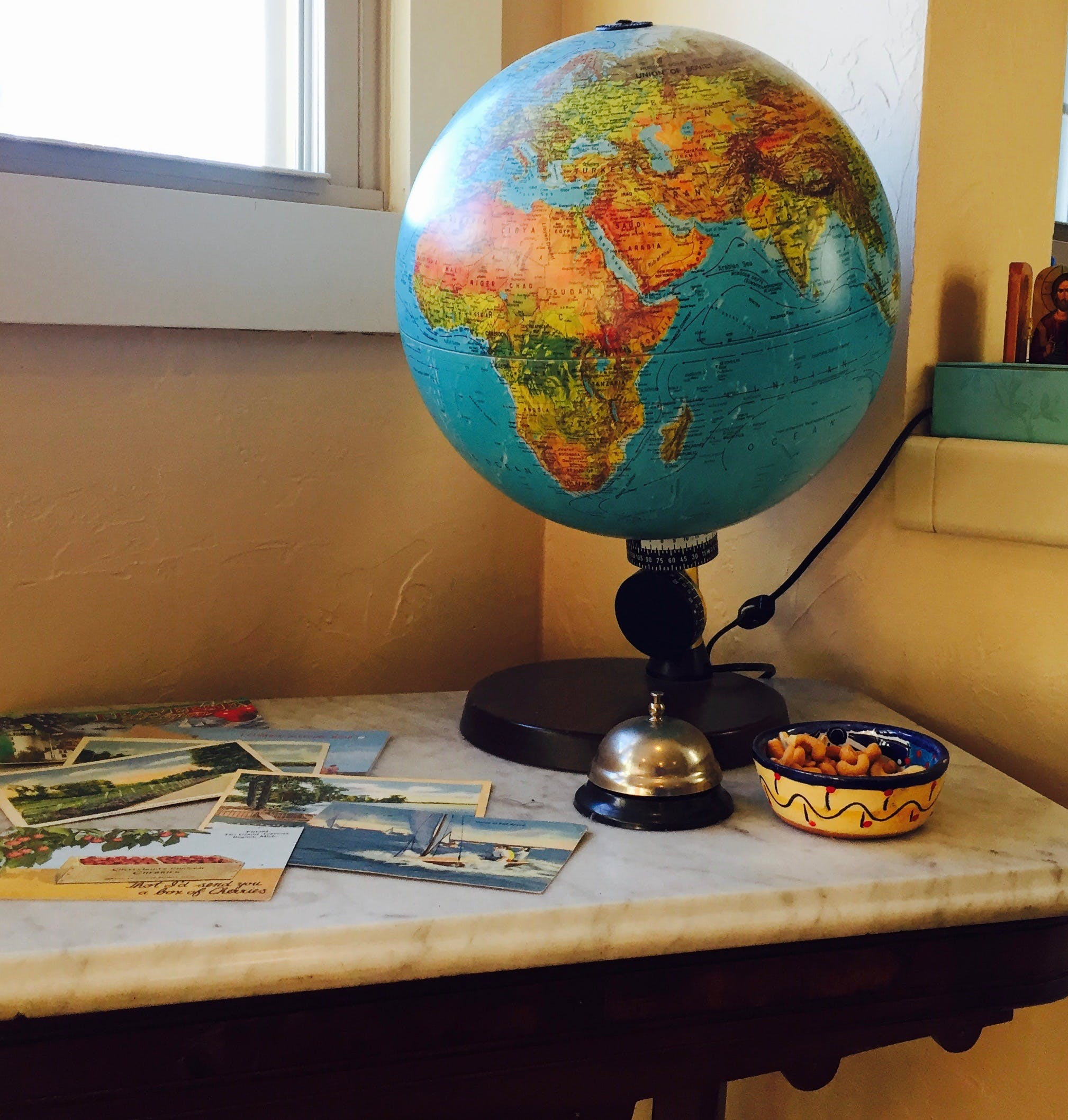 Lighted globe and retro postcards in dining room